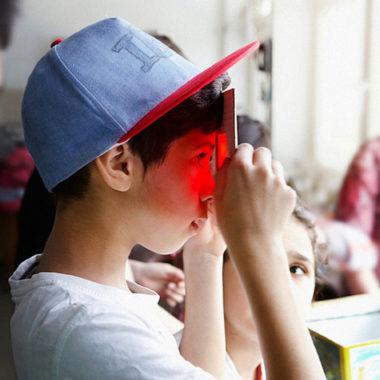 Junge schaut durch rote Scheibe im Museum // HIMBEER