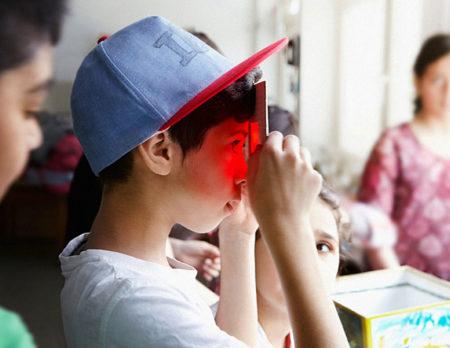 Kreativ Kindergeburtstag in Berlin feiern: Junge schaut durch rote Scheibe im Museum // HIMBEER