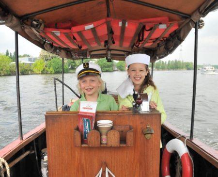 Zwei Kinder hinterm Steuerrad auf dem Boot auf der Spree // HIMBEER