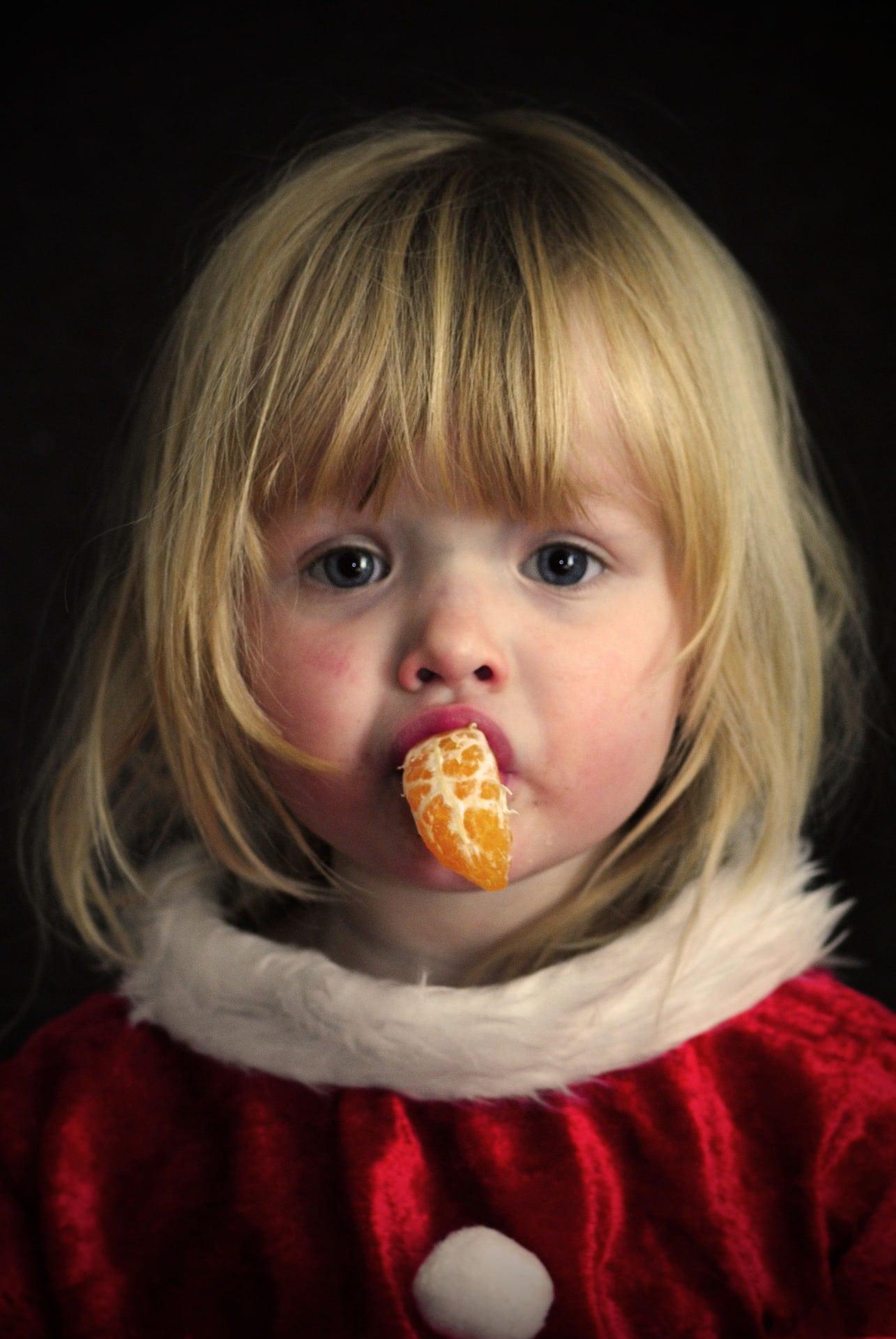 Mädchen mit Mandarine im Mund // HIMBEER